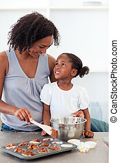 Happy mother helping her daughter cooking biscuits in the...