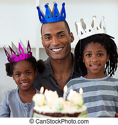 Smiling father with his children celebrating a birthday at...