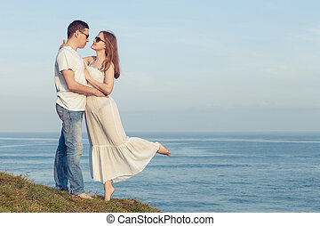 Loving couple standing on the beach at the day time.
