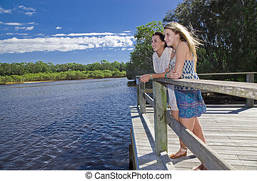 two girls looking out from  viewing platform by the creek