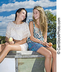 two girls eating apples by the creek on a sunny day