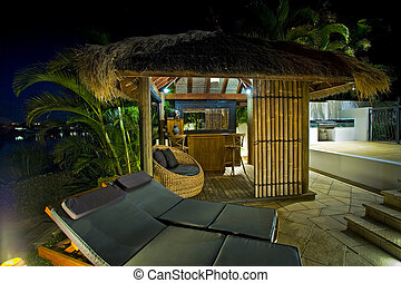 Resort style living with Bali hut with bar and deck chairs