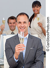 Multi-ethnic business co-workers toasting with Champagne in...