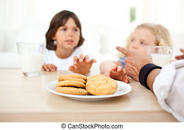 Close-up of adorable children taking biscuits