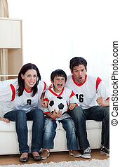 Cheerful young family watching a football match at home