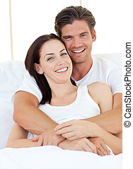Jolly man hugging his wife on their bed