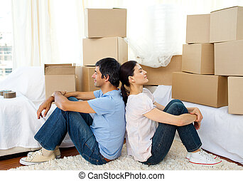 Tired couple relaxing while moving house - Tired couple...