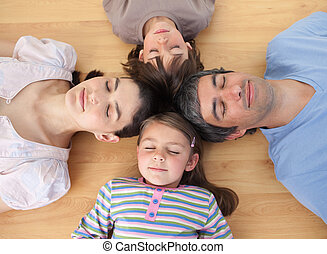 Merry family sleeping lying on the floor with heads together