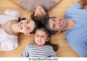 Lively family lying on the floor with heads together