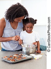 Caring mother helping her girl cooking biscuits in the...
