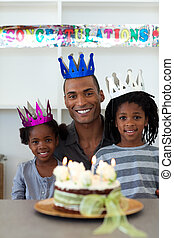 Joyful Afro-american father with his children celebrating a birthday at home