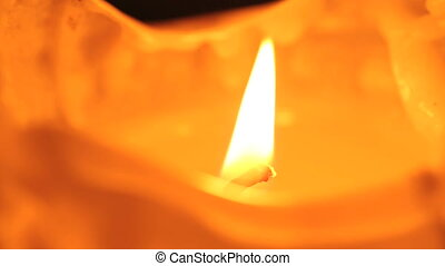 Closeup of a burning candle in front of a dark background