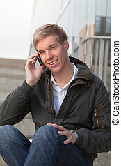 Young guy with cellphone - Young happy blond handsome boy...