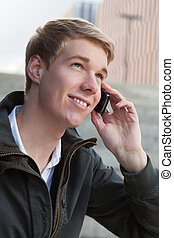 Young guy with cellphone - Young blond handsome smiling man...