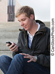 Sending an SMS - Young blond handsome smiling man texting...