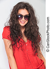 young woman with curly hair wearing sunglasses.