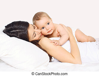 Loving mother lying with cute baby together on the bed at...
