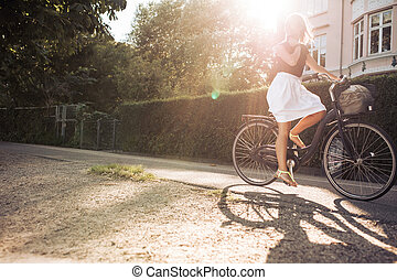 Woman riding a bike on the street - Outdoor shot of a young...