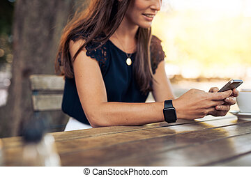 Woman using mobile phone at cafe - Woman typing text message...