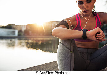 Runner checking her performance on fitness smart watch...
