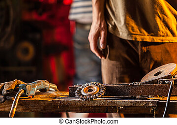 Close-up of worker in workshop with many tools on table