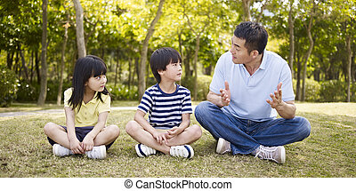 asian father and children talking in park - asian father and...