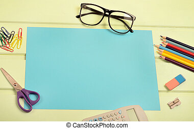 Blue paper with office supply on green wooden table