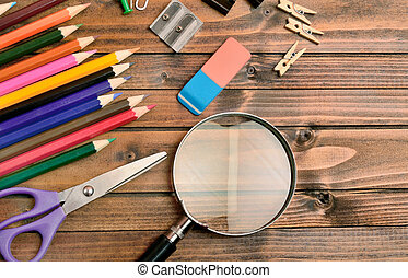 Magnifying glass with office supply on table