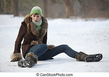 woman slips on snowy road - woman slips and falls down on...