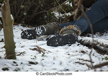 crime scene in snowy forest - unconscious woman lying in...