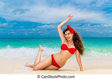Pin up beautiful young woman in red bikini on a tropical...