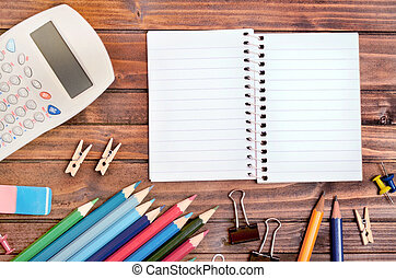 Empty notepad with office supply on wooden table