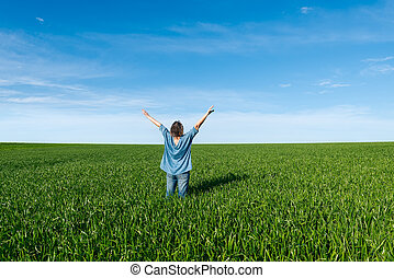 Woman with raised hands  standing back in green field
