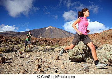 Couple trail running in spectacular volcano landscape on...