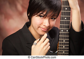 Multiethnic Girl Poses with Electric Guitar - Multiethnic...