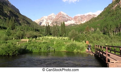 Hiking to the Maroon Bells - a hiker crosses a bridge...