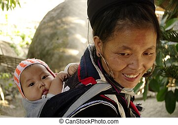 Black Hmong woman and baby - A Black Hmong woman and her...