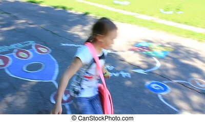 girl runs on the childish drawings on the asphalt of street