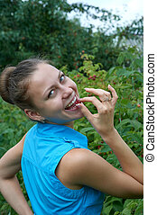 young girl in garden with raspberries in your mouth smiles