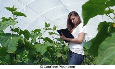Young girl agronomist records observations.Young agronomists...