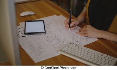 Young female architect working on blueprint - Young female...