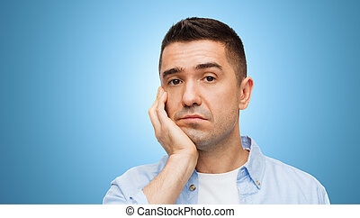 bored middle aged man face over blue background