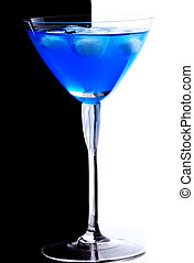 Blue cocktail with ice cubes against black and white