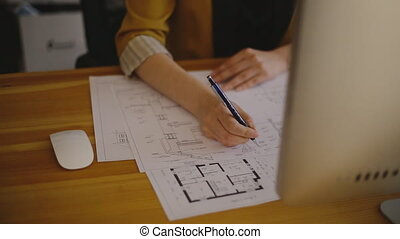 Young female architect drawing line on blueprint. - Young...