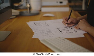 Attractive Young female architect working on blueprint -...