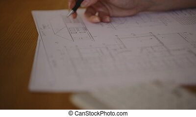 Hands Young female architect working on blueprint - close-up...