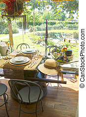 Dining table set for two people overlooking the garden in...