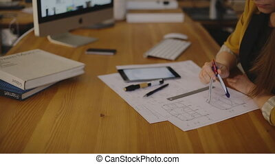 Female Architect Studying Plans In Office using the compass...
