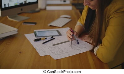 Young female architect working on blueprint using the...