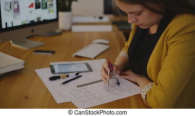 Portrait Young female architect working on blueprint using the compass and enter the data into an electronic tablet